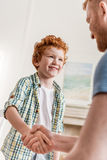 Father and smiling son shaking hands. Side view of father and smiling son shaking hands Royalty Free Stock Photo