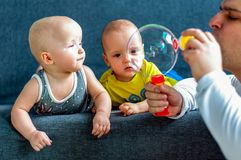 Father with soap bubbles in the foreground. In the background are twins, a boy and a girl of 7 months. Maternity. Father with soap bubbles in the foreground. In stock photo