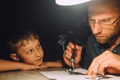 Father soldering with electric soldering iron and his little son. Watches how he works Royalty Free Stock Photo