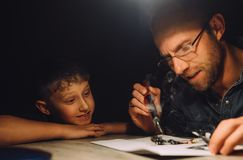 Father soldering with electric soldering iron and his little son Stock Images