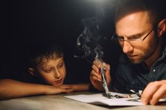 Father soldering with electric soldering iron and his little son. Watches how he works Royalty Free Stock Images