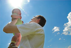 Father with son. Young father holds his son on blue sky background royalty free stock photos