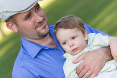 Father and Son. A proud young father holding his cute baby boy with a smile on his face stock image