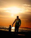Father and son. A father walking into the sunset with his son Royalty Free Stock Photos