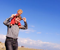 Father and son. Father carring his son piggiback. Blue sky on the background stock photos