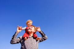 Father and son. Father carrying his son piggiback. Blue sky on the background royalty free stock photography