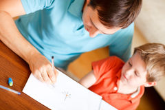 Father and son. Young father and his son drawing together stock images