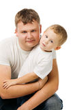 Father and  son. Daddy with the son in white T-shirts, the daddy embraces the son, isolated on white Stock Images