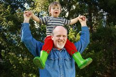Father and son. Father with son on shoulders and trees in background Royalty Free Stock Photography