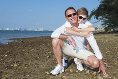 Father and Son. Lifestyle image on the shoreline of Miami's Biscayne Bay with skyline and bridge in the background stock photo