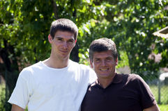 Father and son. Smiling father and teenager son in the garden royalty free stock image