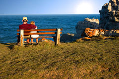Father and son. Sitting on bench staring out over the ocean Royalty Free Stock Photos