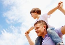 Father and son. Portrait of happy man holding his son on neck on the background of sky Stock Photography