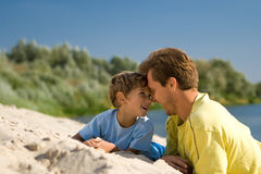 Father and son. The father and the son lie on sandy to river bank and smile Stock Photo