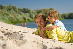 Father and son. The father and the son lie on sandy to river bank and smile Stock Images