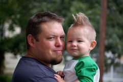 Father and Son. Young father holding his one year old son with a mohawk Royalty Free Stock Photo