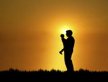 Father and Son 2. Silhouette of father and son at sunset Stock Photo