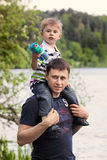 The father and the son. The little boy sits on the shoulders of the father near the lake in the park stock image