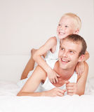 Father and son. Happy family;  father and his little son on the bed at home, relaxing and laughing Royalty Free Stock Photography