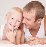 Father and son. Happy family;  father and his little son on the bed at home Stock Image