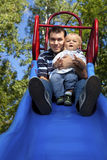 Father and son. On a slide in a park Stock Photos