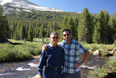 Father and Son. On a hiking or camping trip in the Sierra Nevada Mountains standing by a stream or river in Yosemite National Park Stock Image