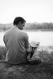 The father and the son. The father and its small son sit on river bank. A kind from a back. A black-and-white photo royalty free stock photography