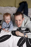 Father and son. On a bed smiling stock photography
