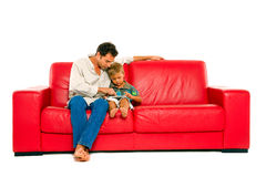 Father and son. Sitting on a red sofa Royalty Free Stock Photography