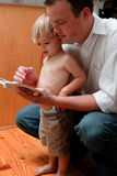 Father and Son. Father looking at a child's book with his son royalty free stock photos