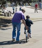 Father and son. Father is teaching his son to ride a bicycle Stock Image