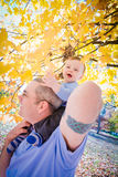 Father and Son. A baby boy having fun playing with his dad outside. The boy is sitting on his dad's shoulders fascinated with the colorful leaves Royalty Free Stock Photo