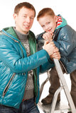 Father and Son. Happy Father and Son on the White Background.They Dressed in Similar Warm Jackets Royalty Free Stock Photography