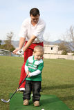 Father and Son. Toddler and his father practising on the golf driving range.  Focus on the child Royalty Free Stock Image