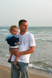 Father and son. Father holds son on hands at sea Royalty Free Stock Image