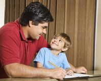 Father and son. Hispanic father and   son doing homework and making eye contact Stock Images