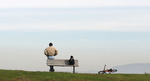 Father and son. Standing on a park bench with the child bike on the side Stock Image