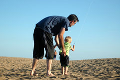 Father and Son. Flying a kite on the beach royalty free stock photography