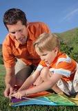 Father & Son. Young white father helping son assemble a kite at a park during summer Royalty Free Stock Images