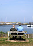 Father and Son. Sit by the harbour and watch the boats, realising how quickly time passes by and how many lovely memories they have to share Stock Images