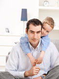 Father and son. Father sitting on floor, his son embracing from behind, smiling Stock Photo