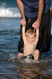 Father and Son. Boy playing in the ocean with his dad royalty free stock photography