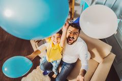 Pretty happy man and boy fooling with balloons. Father and son activity. Cheerful jolly boy and men having fun with balloons while laughing stock photos