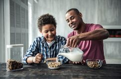 Father and son. Afro American father and son in casual clothes are smiling while eating muesli at the wooden table together at home royalty free stock photos