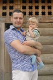 Father with son. Against wood wall outside royalty free stock photography