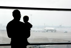 Father and son in the airport. Father and son looking at airplanes Stock Image