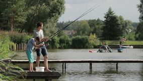 Father and son angling with spinning rod at lake stock video