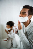 Father and son applying foam on face together Royalty Free Stock Images