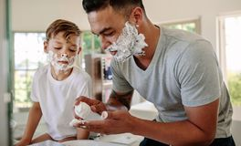 Father and son applying shaving foam on their faces. In bathroom. Man and little boy putting shaving foam on their faces while shaving in bathroom Royalty Free Stock Photography
