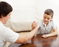 Father and son arm wrestling. Dad play with child Stock Photo